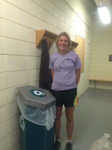 Cross Country runner Eliza Matt stands next to one of the new locker room recycling bins