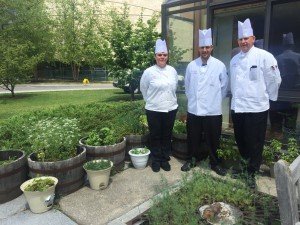 Assistant Catering Chef Charlotte Clark, Catering Cook James Godfrey , & Catering Chef Jim Guiden amidst the herbs on the patio of the Faculty House
