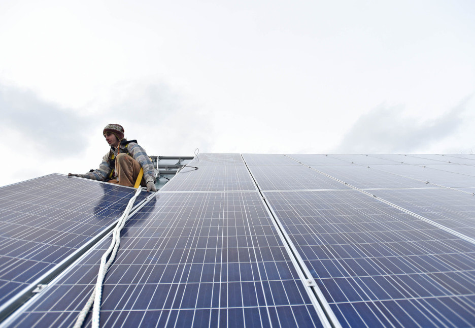A worker installing a solar panel on a building