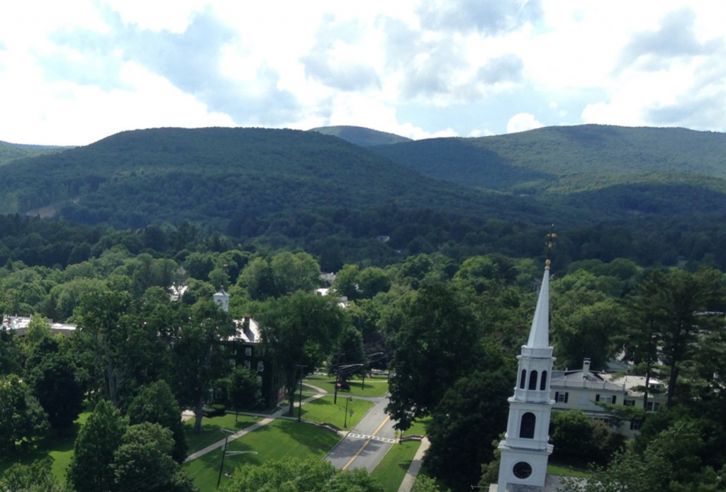 An aerial view of Williamstown with a church in the foreground and mountains in the background