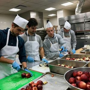 Students cutting apples in an industrial kitchen.